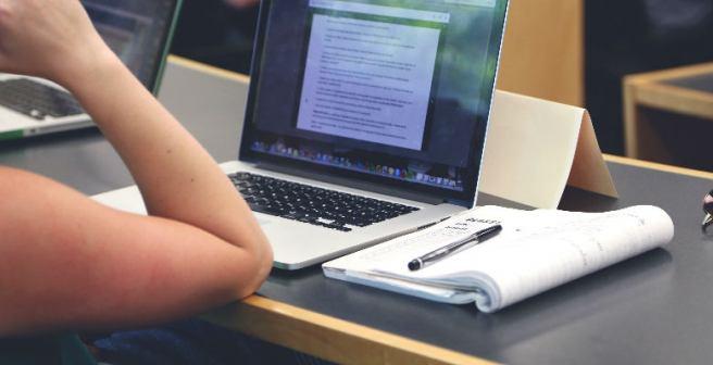 pessoa estudando com um notebook e um livro