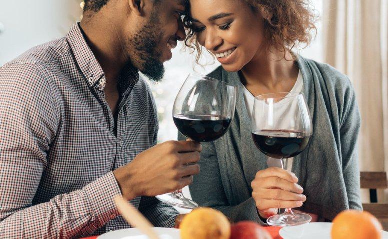 imegam de um casal be próximos e segurando taça de vinho